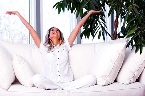 kobieta siedząca na kanapie z rękami uniesionymi do góry