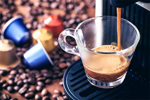 strumień kawy lejący się do filiżanki z ekspresu na kapsułki