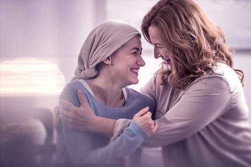 Kobiety przytulają się - jedna ma chustę na głowie