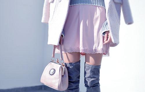 kobieta różowej spódniczce z torebką i z zarzuconym płaszczem