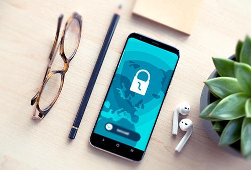 telefon leżący na biurku z okularami, długopisem i sulukentem
